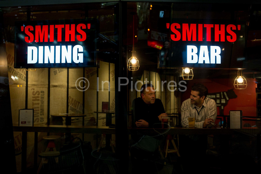 Two men drink and talk in the window of Smiths Bar on Cannon Street in the heart of the Square Mile, the capitals historical and financial centre, on 1st November 2017, in the City of London, England.