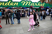 Mother Louise Irwin-Ryan with her daughter Georgia (11, wearing a pink Lolita dress) walk past the famous sign for Camden market whilst spending a day out together in Camden Town, North London. Louise is on various benefits to help support her family income, and housing, although recent government changes to benefits may affect her family drastically, possibly meaning they may have to move out of London. Louise Ryan was born on the Wirral peninsula in 1970.  She moved to London with her family in 1980.  Having lived in both Manchester and Ireland, she now lives permanently in North London with her husband and two children. Through the years Louise has battled to recover from a serious motorcycle accident in 1992 and has recently been diagnosed with Bipolar Affective Disorder. (Photo by Mike Kemp/For The Washington Post)