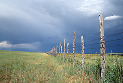 Rustic fence seperating cattle pastures under a stormy sky in Las Vegas New Mexico