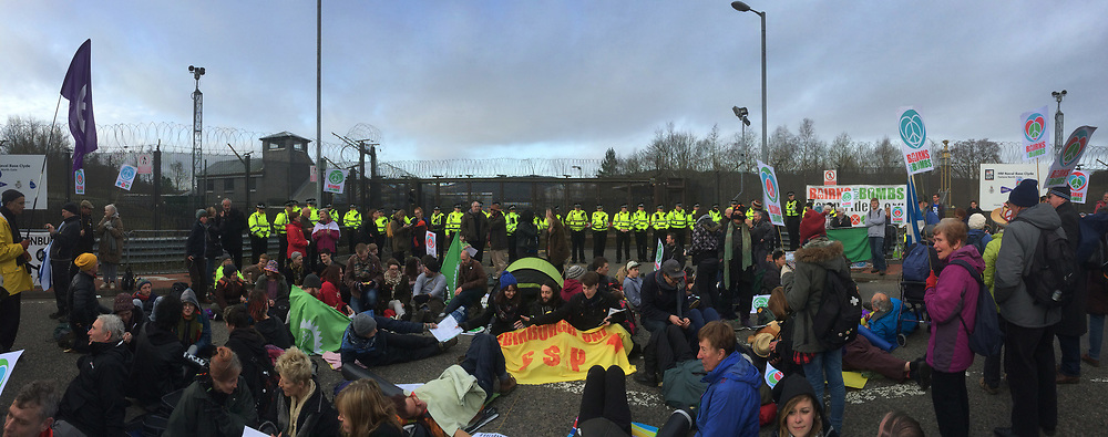 People sitting in front of a line of police officers at the North Gate of Her Majesty's Naval Base, Clyde, Faslane, Scotland, during a blockade by around 150 people protesting against the Trident nuclear missile system. The protestors managed to shut down the base, preventing workers, contractors and naval personnel from accessing the site. A decision was due to be made by the UK government in 2016 whether to replace the Trident submarine system.