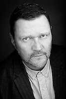A thought provoking actor headshot in black and white featuring Actor Ian Puleston-Davies