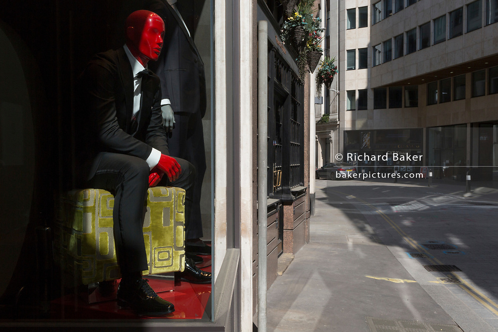 As the UK government's lockdown restrictions during the Coronavirus pandemic continues, and number of UK reported cases rose to 138,078 with a total now of 18,738 deaths, a mannequin appears to be looking out of the display window of a menswear retailer on to deserted streets and normally thriving businesses in the City of London, the capital's financial district, on 23rd April 2020, in London, England.