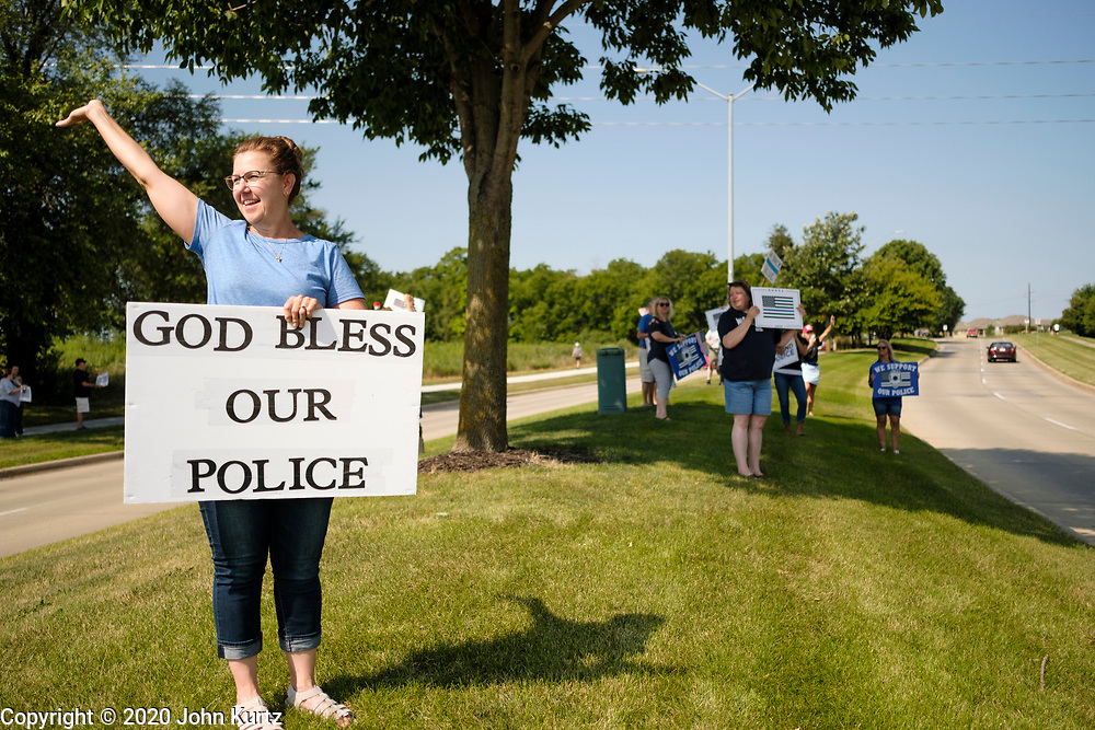 """08 AUGUST 2020 - WEST DES MOINES, IOWA: People line Mills Civic Parkway in front of the West Des Moines police station during a rally in support of police and law enforcement. About 100 people gathered at the West Des Moines Law Enforcement Center to rally in support of law enforcement. The rally was organized by """"Uplifting Our Police,"""" a local organization that supports law enforcement. They rallied at Des Moines Police headquarters in July. They are planning similar rallies at police stations in the Des Moines metropolitan area.     PHOTO BY JACK KURTZ"""