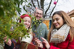 Friends holding gifts and mistletoe twigs
