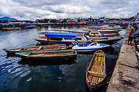 Indonesia, Sulawesi, Manado. Colourful boats in Manado harbour. Tha market in the background.