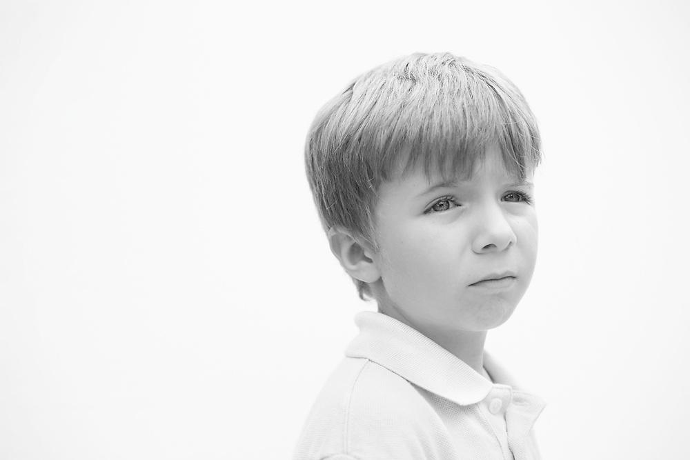 Black and white portrait photograph of sad bullied boy