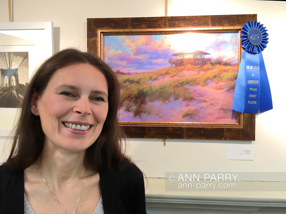Manhasset, New York, U.S. April 7, 2017. Painter stands at her painting that won First Place, at Reception for The Art Guild exhibition is held at Elderfields Preserve.