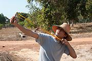 Thai man uses a slingshot to hunt birds