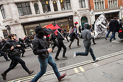 © Licensed to London News Pictures . FILE PHOTO DATED 20/10/2012 of a Black Bloc of protesters breaking away from a TUC demonstration and running along Regent Street in London , as reports circulate that black bloc tactics may be employed by protesters seeking to demonstrate during the funeral of former British Prime Minister Margaret Thatcher . Photo credit : Joel Goodman/LNP