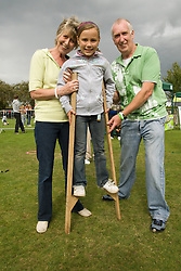 Grandparents helping their Granddaughter to learn to use stilts at a Parklife summer activities event,