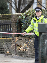 © Licensed to London News Pictures. 22/01/2018. London, UK. A damaged wall is seen near a police officer in Romford Road after a shooting incident. Roads are closed after a man was shot in the head last night. Photo credit: Peter Macdiarmid/LNP