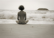 Rear view of nude woman sitting crosslegged on beach meditating with island in the background