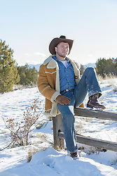 sexy cowboy leaning on a spilt rail fence in the snow