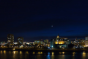 Just after sundown, Sunday, April 26, 2009, a slender crescent Moon lines up with Mercury and the Pleiades star cluster for a three-way conjunction viewed through scattered cloud over downtown Saskatoon, Saskatchewan.