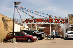 A man on a bicycle considers an extended cab truck in a used car lot