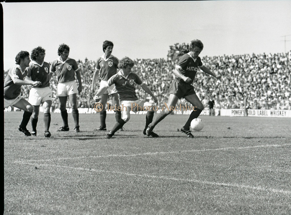 League of Ireland vs Liverpool FC.    (M87)..1979..18.08.1979..08.18.1979..18th August !979..In a pre season friendly the League of Ireland took on Liverpool FC at Dalymount Park Phibsborough,Dublin. The league team was made up of a selection of players from several League of Ireland clubs and was captained by the legendary John Giles. Liverpool won the game by 2 goals to nil..The scorers were Hansen and McDermott...Image shows Phil Neal attempting to clear the ball as the Irish attackers close in.