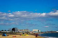 A sunny day at Old Orchard Beach, in Maine with a gull flying in a blue sky.