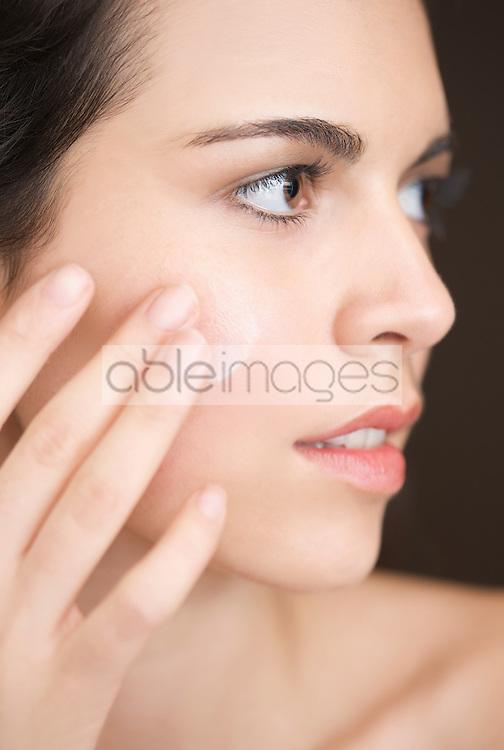 Close up of a woman applying moisturiser on her face