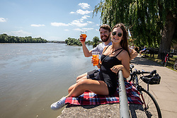 © Licensed to London News Pictures. 22/06/2020. London, UK. Pub goers Simon O'Brien 25 and Megan Van Dessel 26 from Kennington, enjoy a takeaway pint at the Black Lion Pub along the banks of the River Thames in Hammersmith, West London as forecasters predict a warm week ahead with temperatures set to reach over 30c. Tomorrow, Prime Minister, Boris Johnson is expected to give the green light to loosening of the 2 metre social distancing rule with hotels and campsites set to reopen in the next 2 weeks. Photo credit: Alex Lentati/LNP