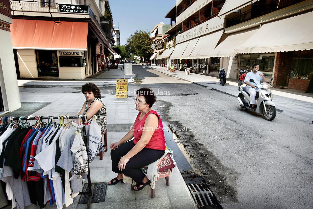 Griekenland.Peloponnesos.Olympia.29 augustus 2007..Winkeleigenaars zitten werkeloos voor hun zaak in een vrijwel lege straat door  het wegblijven van toeristen als gevolg van de recente bosbranden in de buurt.