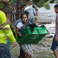 A girl salvages belongings from her home as the Río Blanco in San Pedro Sula rose and swelled with fast-running water as hurricane Iota pushed into Honduras. Precarious housing on the riverside began to be washed away and people rushed to save their belongings.