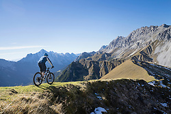 Mountain biker riding on uphill in alpine landscape, Tyrol, Austria