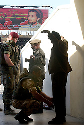 KABUL,AFGHANISTAN - SEPT. 8: German ISAF forces check Afghan workers before they are allowed to enter  Kabul Sports Stadium September 8, 2002 in preparation for the events tied to tomorrow's  anniversary of the death of Ahmad Shah Massoud in Kabul, Afghanistan. (Photo by Ami Vitale/Getty Images)
