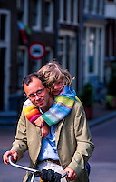Father and daughter riding bicycle on Brouwersgracht, Amsterdam, the Netherlands