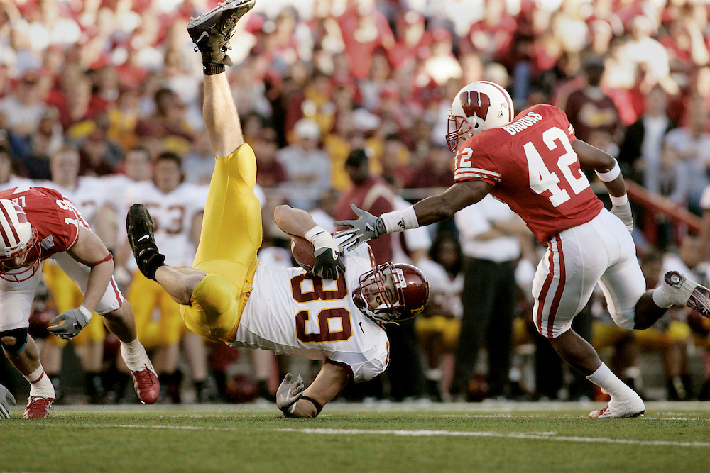 Minnesota's Matt Spaeth, middle, is flipped over by Wisconsin's Jim Leonhard as Wisconsin's Robert Brooks (42) gets ready to dive in as Wisconsin plays Minnesota at Camp Randall Stadium in Madison, Wisconsin.