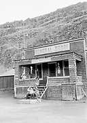 9305-B7045. Indian children sit on steps and drink soft drinks at the Celilo General Store and Post Office. The store owner is Charles E Frye, and his wife Laura B. is holding their granddaughter Susan. April 1940