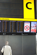 "An upright picture of a departures information board at Heathrow Airport's Terminal 5. A lady passenger stands motionless to read the details of flight departure times to echo that of a Vodafone advertisement containing a figure of a man standing erect on a beach, a generic scene of a person on holiday taking advantage of low mobile phone charges in mainland Europe.  Both the man and the woman are on opposite sides of the picture and we see a large letter C that denotes the check-in zone of this 400 metre-long terminal that has the capacity to serve around 30 million passengers a year. From writer Alain de Botton's book project ""A Week at the Airport: A Heathrow Diary"" (2009)."