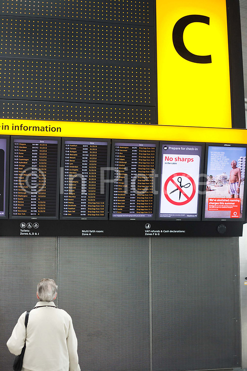 """An upright picture of a departures information board at Heathrow Airport's Terminal 5. A lady passenger stands motionless to read the details of flight departure times to echo that of a Vodafone advertisement containing a figure of a man standing erect on a beach, a generic scene of a person on holiday taking advantage of low mobile phone charges in mainland Europe.  Both the man and the woman are on opposite sides of the picture and we see a large letter C that denotes the check-in zone of this 400 metre-long terminal that has the capacity to serve around 30 million passengers a year. From writer Alain de Botton's book project """"A Week at the Airport: A Heathrow Diary"""" (2009)."""