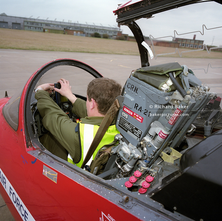 A line engineer technician, prepares a Mk 1 Hawk jet of the Red Arrows, Britain's RAF aerobatic team at RAF Scampton, Lincolnshire. Sitting in a Martin-Baker ejection seat, the workplace of a highly-trained RAF pilot, the man fixes an item on to the instrument panel before another arduous flight at the team's base in Lincolnshire, England. The man is a member of the team's support ground crew (called the Blues because of their distinctive blue overalls worn at summer air shows). The team's support ground crew who outnumber the pilots 8:1 and without them, the Red Arrows couldn't fly. Eleven trades are imported from some sixty that the RAF employs and teaches.