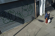 A woman looks at the ground alongside graffiti on the shutters of a closed local business in Camberwell, on 29th March 2021, in London, England.