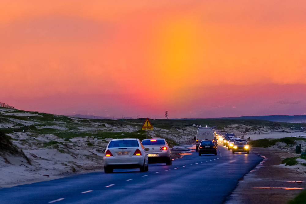 A rainbow behind cars driving after a rainstorm, Strandfontein (near Cape Town), South Africa