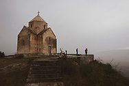 In a wet and cold wind, visitors explore the grounds of Vankasar Church, a 7th-century Armenian church located in the Martakert Region of Republic of Artsakh, not far from Tigranakert fortress.