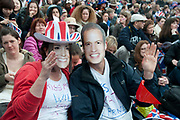 April 29th 2011 Royal Wedding. Trafalgar Square. Couple with Kate and Will masks in the crowd.