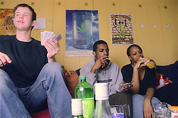 Group of teenagers sitting together drinking alcohol; smoking cigarettes and playing game of cards,