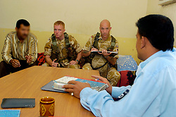 Talkng through an intrepriter employed by the army (Left) Platoon Sgt. Steve Risdale 29 from Kiverton Park In Sheffield (right) holds a routine meeting with the Iraqi Police Service station commander to check on the local policing situation.Inside a small police station in Basrah.<br />5 March 2005<br />Copyright Paul David Drabble