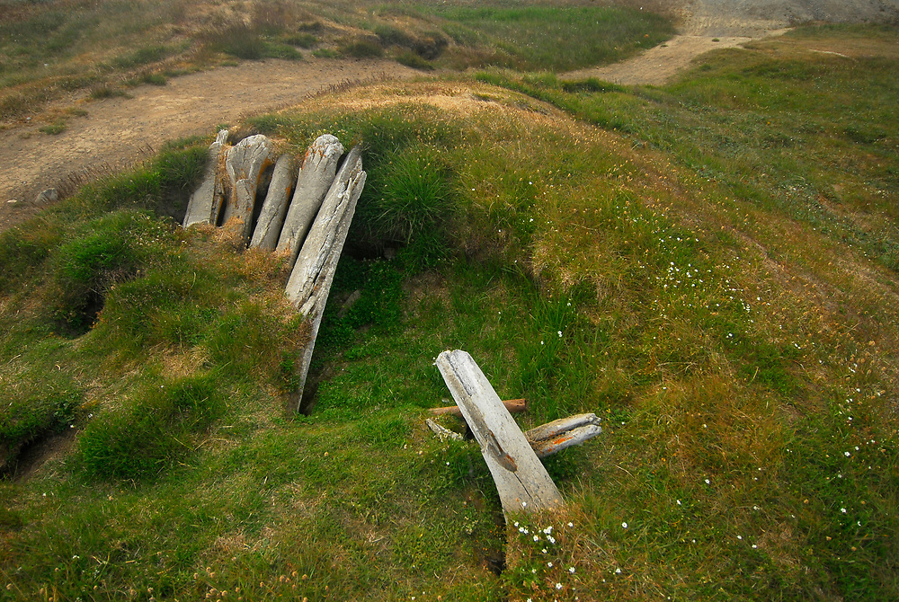 Alaska, Barrow. Remains of old sodhouses in the old village of Barrow, called Ukpeagvik. Due to Fall season storms, the tundra is receding and being swollen by the ocean. The sea ice receds with global warming and Fall storms are storngers, Barrow is losing permafrost and soil.