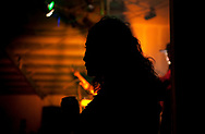 LiLiana Manrique Zavala, of Nayarit, Mexico, watches as other women dance at a local bar.