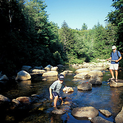 Randolph, NH.A young boy and his grandfather try their luck at fishing on the Moose River in New Hampshire's White Mountains. Androscoggin River watershed.