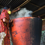 CAPTION: Smoke billows out of one of DESI Power's gasifiers as Bhalo Devi raises its lid, ready to add more biomass for combustion. LOCATION: Behirban, Araria District, Bihar, India. INDIVIDUAL(S) PHOTOGRAPHED: Bhalo Devi.