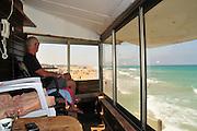 Israel, Haifa, Carmel Beach, Israelis go to the Beach on a warm, sunny day. Lifeguard overlooks the swimmers .