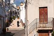 An old man walks in Pisticci, Italy. Pisticci is a town in the province of Matera, in the Southern Italian region of Basilicata.