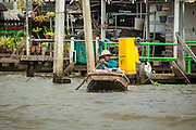 """17 NOVEMBER 2012 - BANGKOK, THAILAND:  A man paddles his canoe on a khlong, or canal, in the Thonburi section of Bangkok. Bangkok used to be known as the """"Venice of the East"""" because of the number of waterways the criss crossed the city. Now most of the waterways have been filled in but boats and ships still play an important role in daily life in Bangkok. Thousands of people commute to work daily on the Chao Phraya Express Boats and fast boats that ply Khlong Saen Saeb or use boats to get around on the canals on the Thonburi side of the river. Boats are used to haul commodities through the city to deep water ports for export.    PHOTO BY JACK KURTZ"""