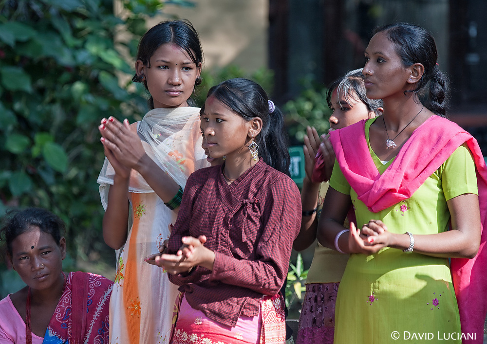 Nepalese ladies clapping while listening a group playing music in Chitwan National Park.