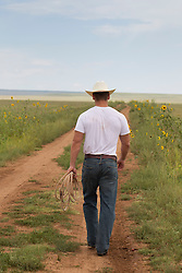Cowboy walking off on a dirt road