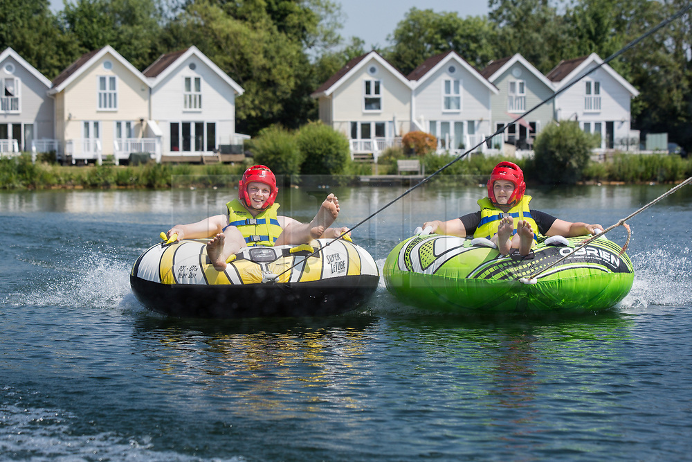 © Licensed to London News Pictures 28/06/2108, Cirencester, UK. Tourists are enjoying the continued hot weather as they are dragged around the lake in inflatable rings at the Lakeside Ski & Wake centre, the Cotswold Water Park near Cirecenster, Gloucestershire. Photo Credit : Stephen Shepherd/LNP