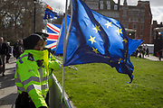 A Muslim Met Police WPC officer stands by the EU flag while patrolling the railings of College Green where TV broadcasters report of the Brexit negotiations, during a pro-EU brexit protest opposite Parliament, on 11th March 2019, in Westminster, London, England.